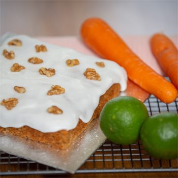 Carrot cake with its ingredients, carrots, and limes